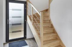 Sas d'entrée avec vue sur la porte d'entrée vitrée et l'escalier en bois