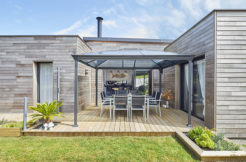 Terrasse en bois et sa pergola qui abrite le salon de jardin
