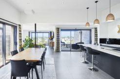 Large pièce de vie incluant la cuisine, la salle à manger et le coin salon