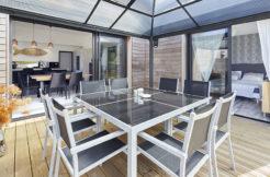 Terrasse en bois avec un salon de jardin abrité grâce à la pergola