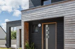 Vue sur la porte d'entrée encadrée par un porche et desservie par une allée en bois