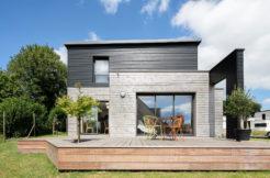 Vue de la maison en bois avec la terrasse et l'arche