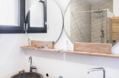 Tendance bois et minéral pour cette salle d'eau équipée d'un meuble double vasque et miroir