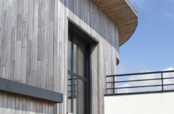 Vue de l'étage et de la toiture à avancée courbe en zinc et en bois