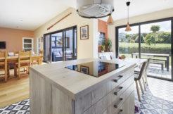 La cuisine semi-ouverte donne sur la terrasse et la salle à manger