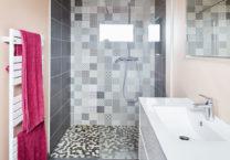 La salle d'eau et sa douche à l'italienne avec ses carreaux de faïence