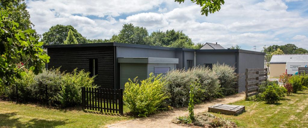 Une maison en bois écologique avec son récupérateur d'eaux pluviales