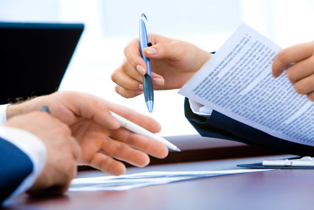 conseiller commerciale avec une cliente qui tient un stylo et une feuille dans ses mains