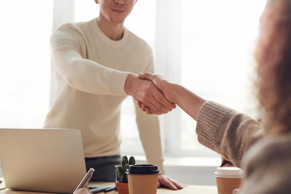 Deux personnes qui se serrent la main dans un bureau
